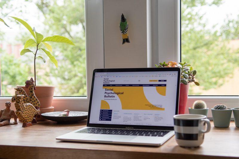 窓際に置かれたパソコンとコーヒー