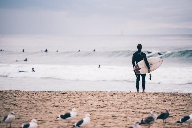 海辺に佇むサーファー