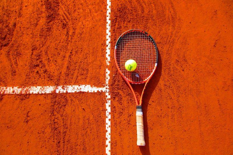 クレーコートに置かれたテニスラケットとボール