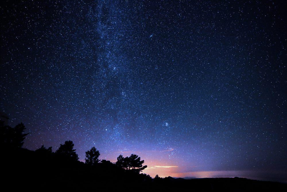 日が沈む大地と満天の星空